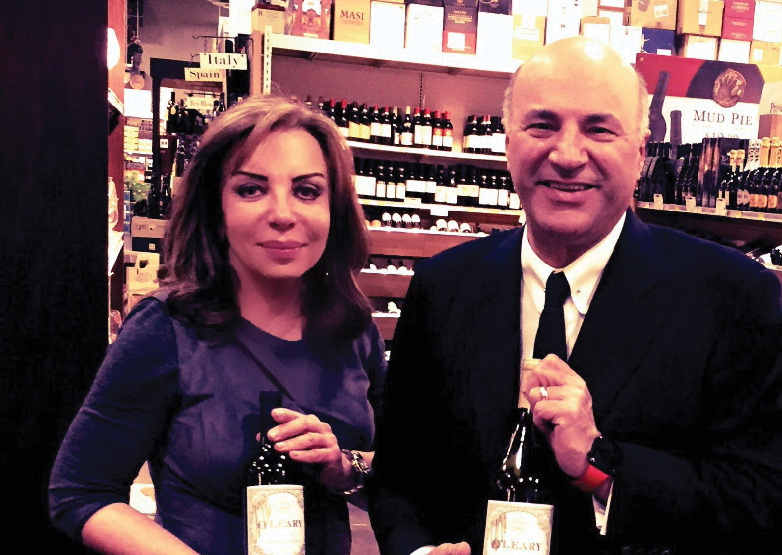 Anne Marie Harrison with Kevin O'Leary standing in her wine store each holding a bottle of wine.