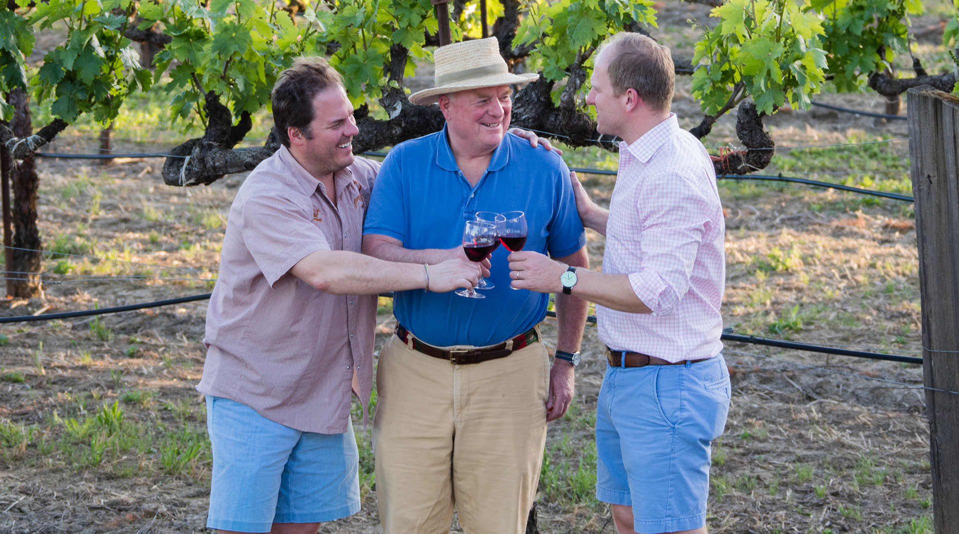 Joe Donelan toasting wine glasses in vineyard with sons.