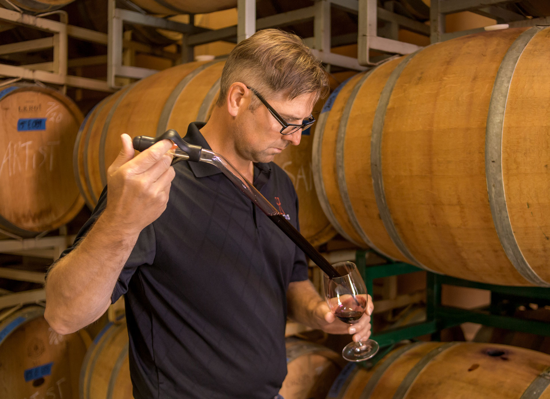 Ned Morris testing wine in front of barrels of wine.
