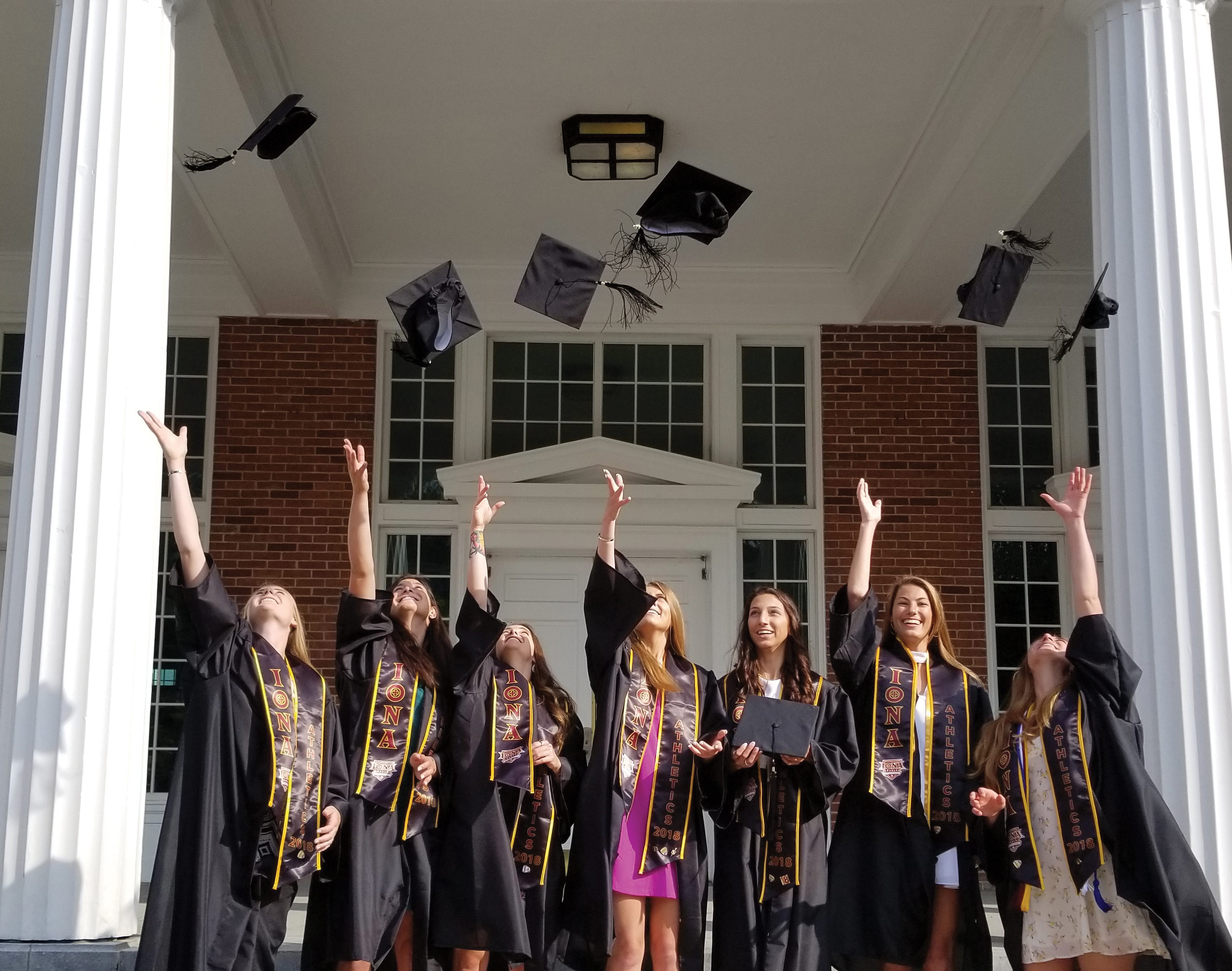 Seven students in front of Spellman hall throwing their graduation caps in the air.