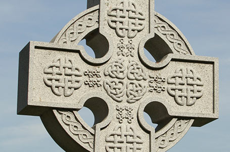 Stone Celtic cross with a blue sky background