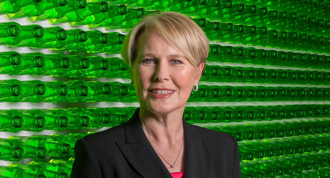 Margaret C Timoney in front of a wall of Heineken bottles.