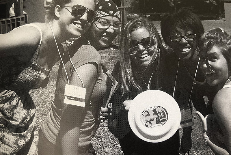 Women smile and pose with their frisbee.