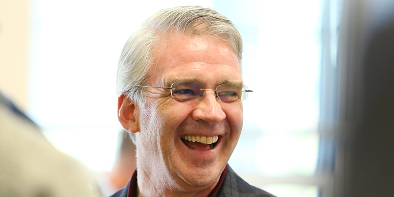 Seamus Carey laughing and smiling widely at an event.