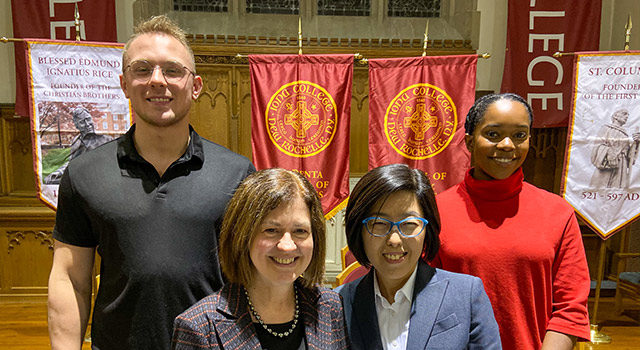 Faculty and students pose in front of banners to celebrate the induction of students to the national honors society.