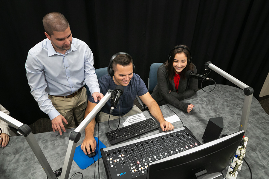Joe teaches students how to use the podcast equipment in the media studio.