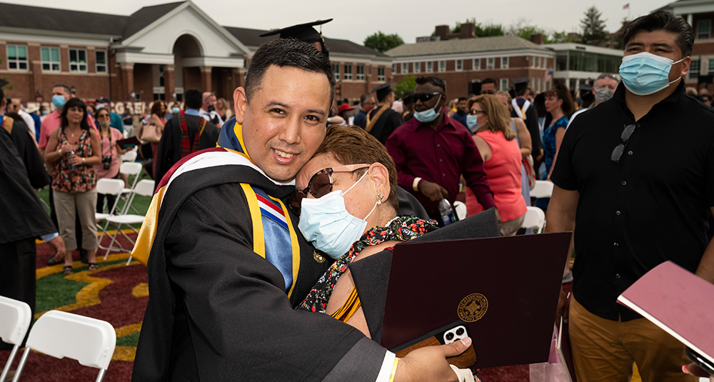 Billy Falla hugs his family member at the commencement ceremony.