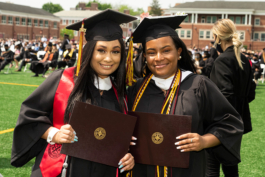Two graduates in regalia hold their diplomas at the 2021 in-person recognition ceremony.